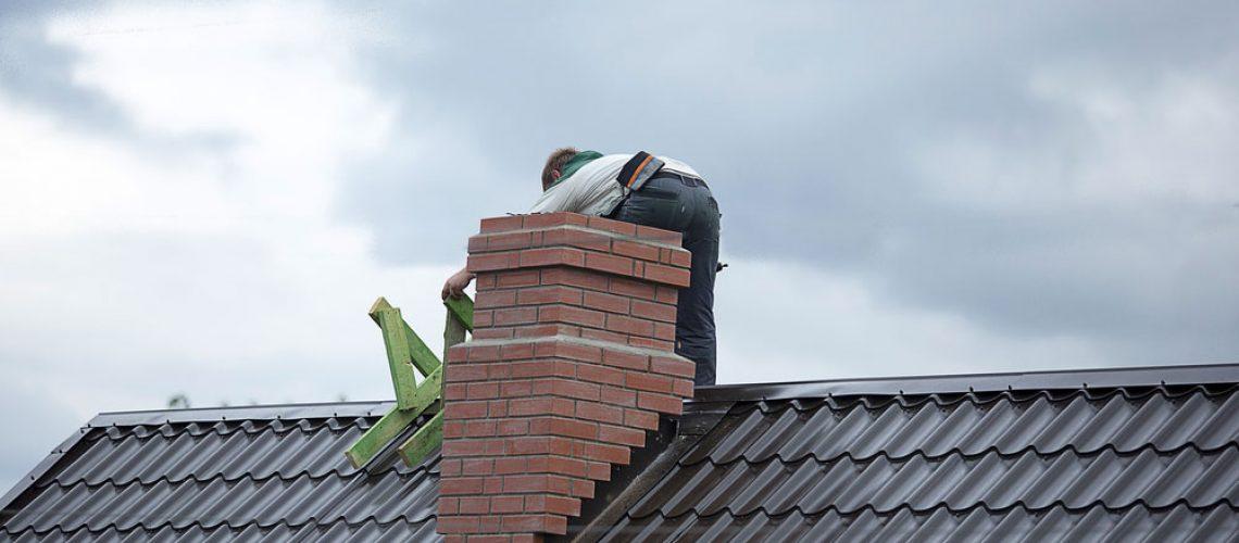 Wildlife control service man installing chimney cap
